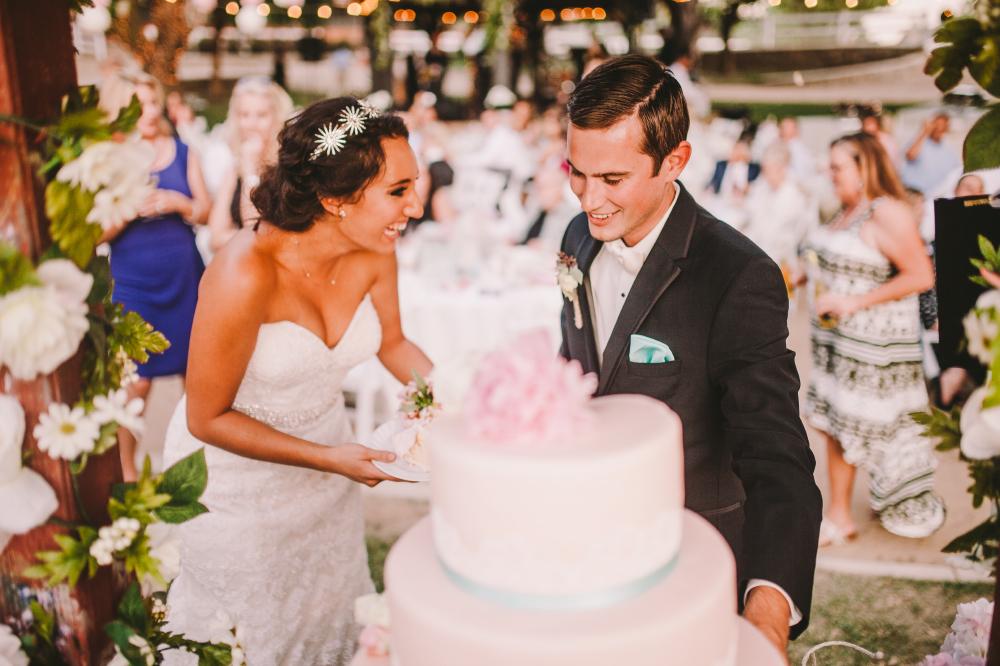 san diego wedding   photographer   newly wed couple laughing cutting into wedding cake