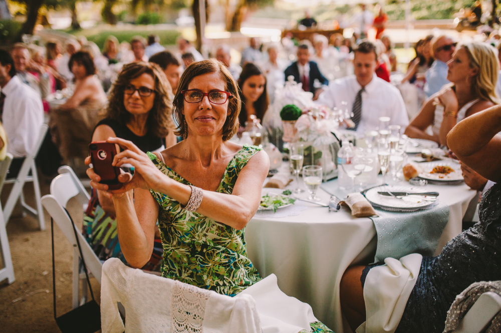 san diego wedding   photographer   crowd in round table with woman in forefront taking a picture