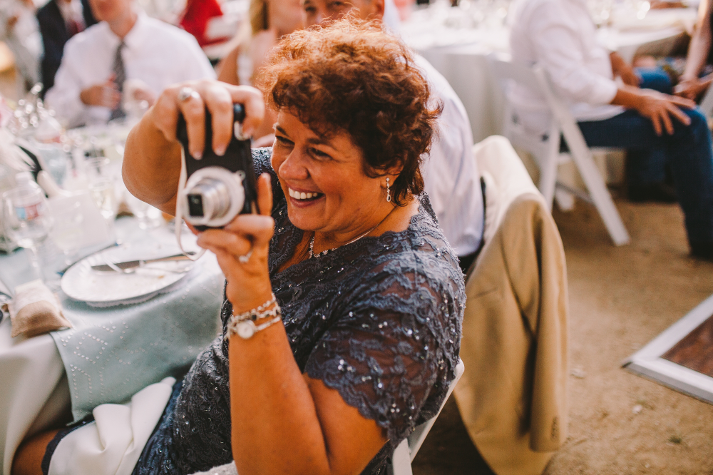 san diego wedding   photographer   woman in blue dress smiling taking picture with digicam