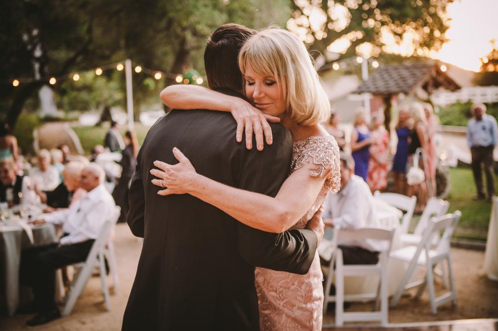 san diego wedding   photographer   blonde woman hugging man in suit while dancing