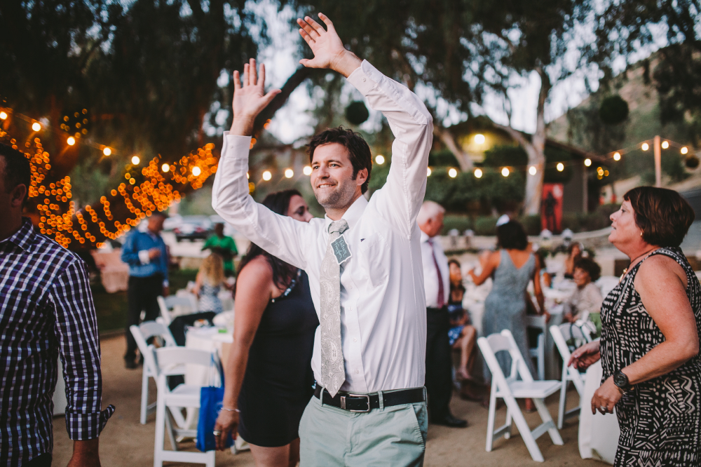 san diego wedding   photographer   man in white shirt and grey tie dancing with arms up high