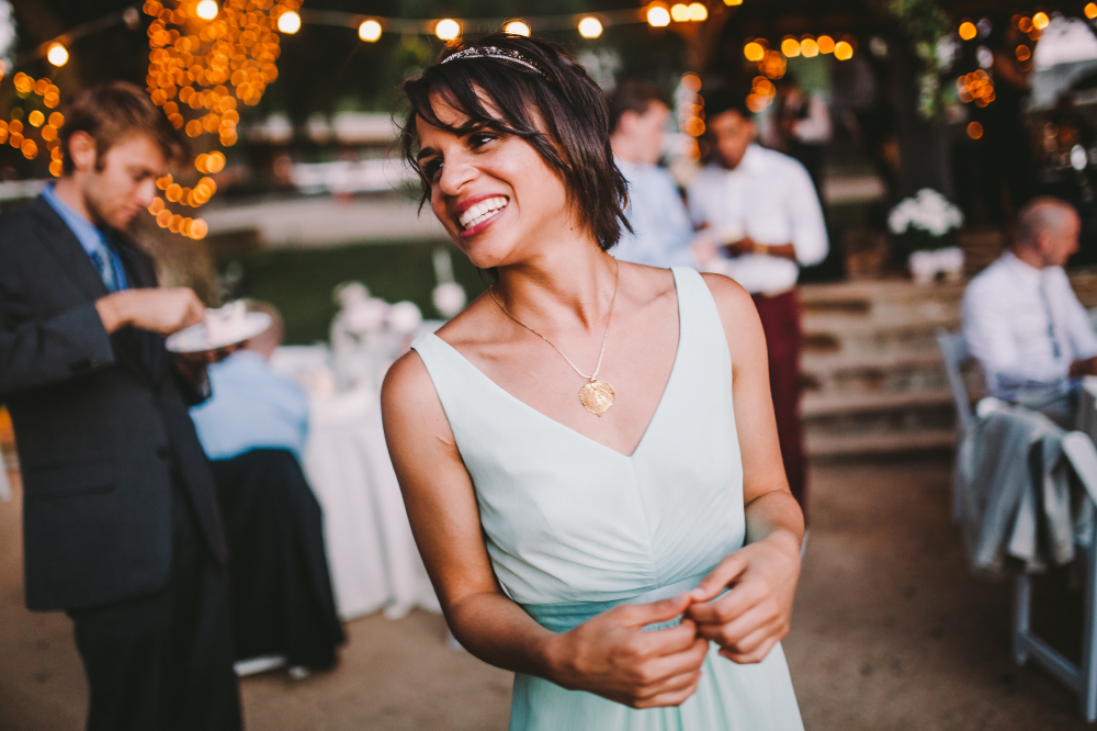 san diego wedding   photographer   woman in white top and light blue skirt smiling looking to her   side