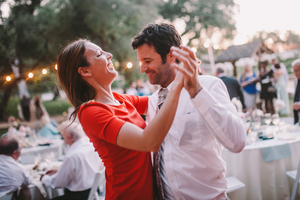 san diego wedding   photographer   man in white shirt dancing with woman in red dress while   laughing