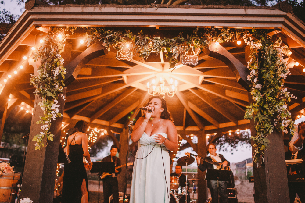 san diego wedding   photographer   woman in white dress singing in front of band