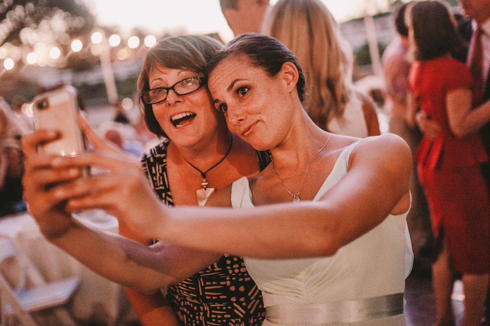 san diego wedding   photographer   woman in white dress taking a selfie with middle aged woman