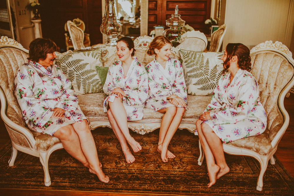 san diego wedding   photographer   bridesmaids in floral robes sitting on sofa