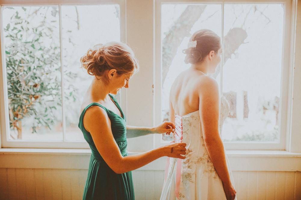 san diego wedding   photographer   woman in teal helping bride zip up wedding dress