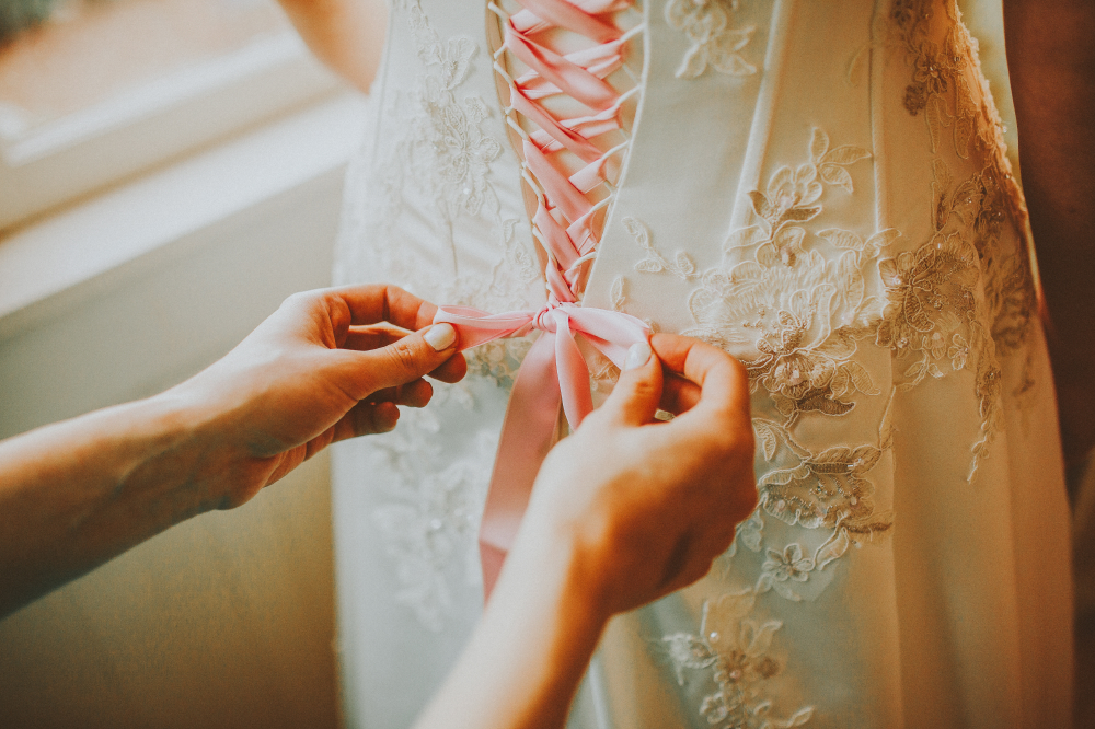 san diego wedding   photographer   woman's hands fixing wedding dress' back