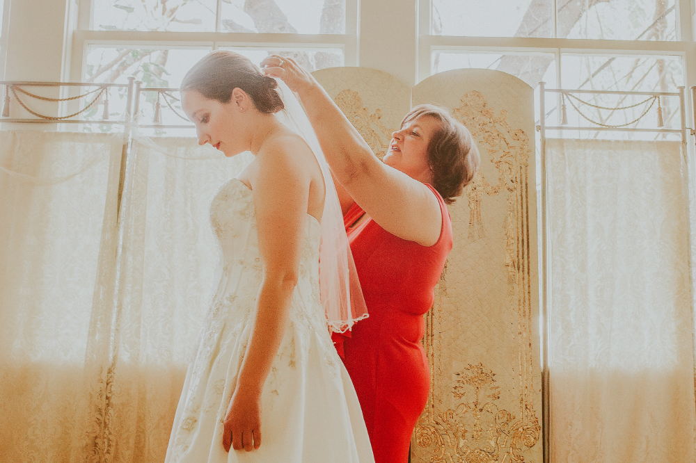 san diego wedding   photographer   woman in red putting on veil on bride