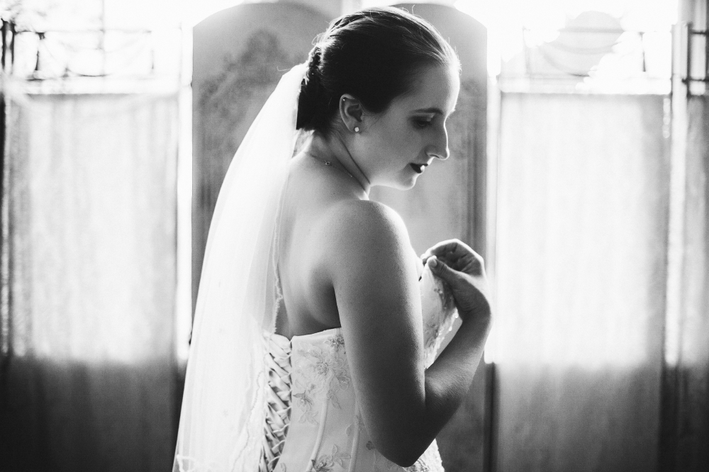 san diego wedding   photographer   monotone shot of bride in wedding dress looking down to her   right