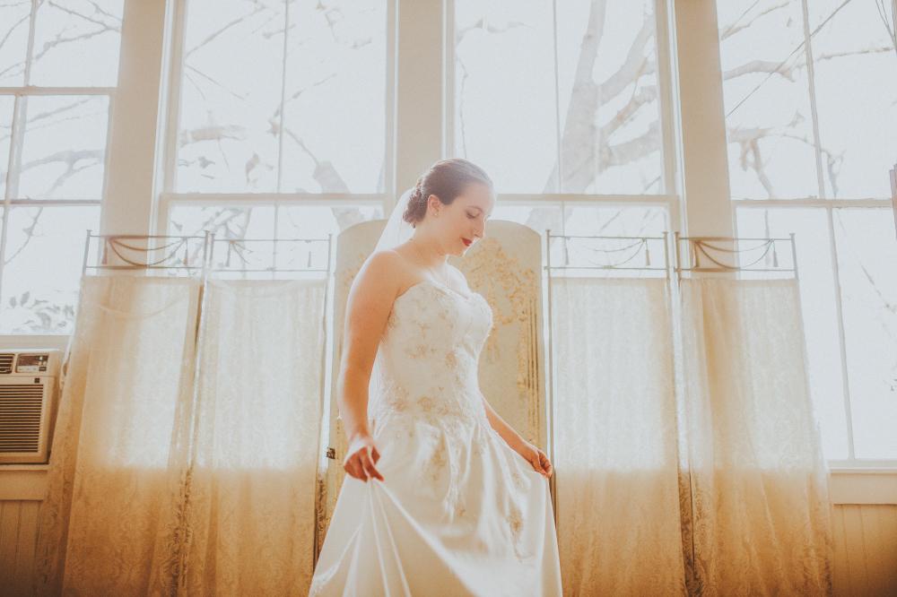 san diego wedding   photographer   bride in wedding dress looking down in front of dresser setup