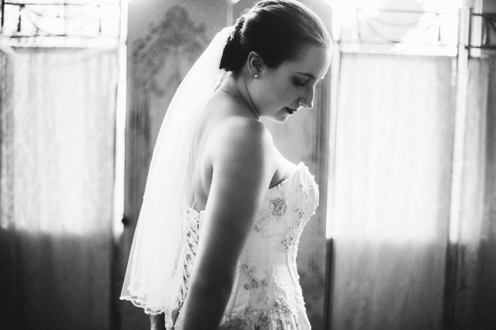 san diego wedding   photographer   monotone shot of bride in wedding dress with arm behind her