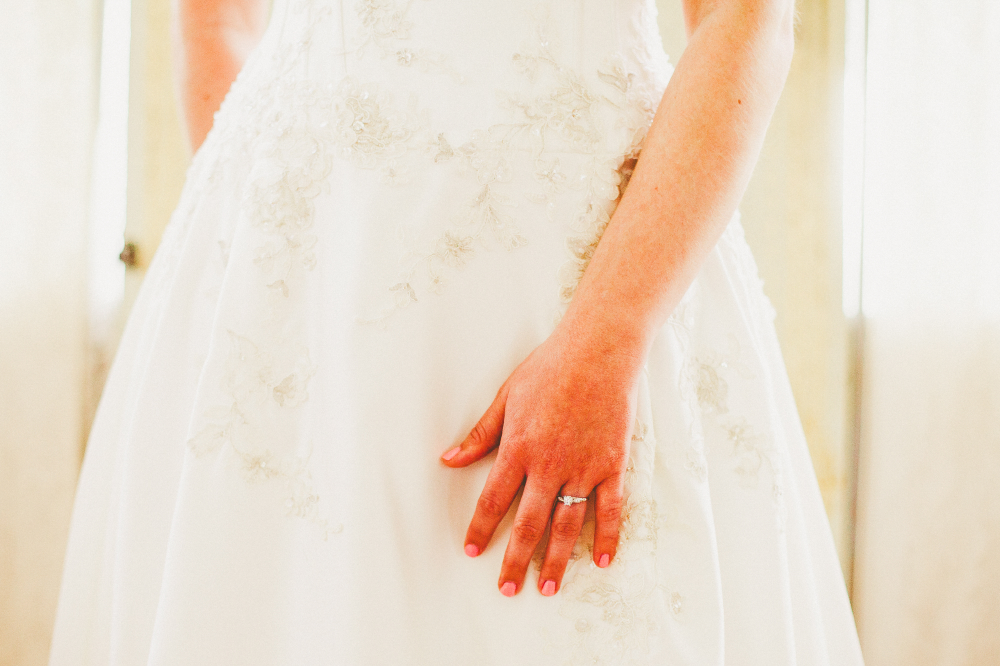 san diego wedding   photographer   torso of bride in wedding dress with hand with ring in view