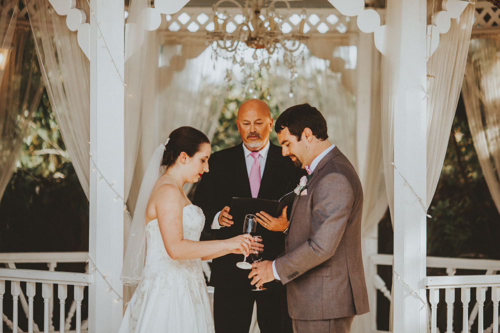 san diego wedding   photographer   bride and groom pouring something out of wine glasses