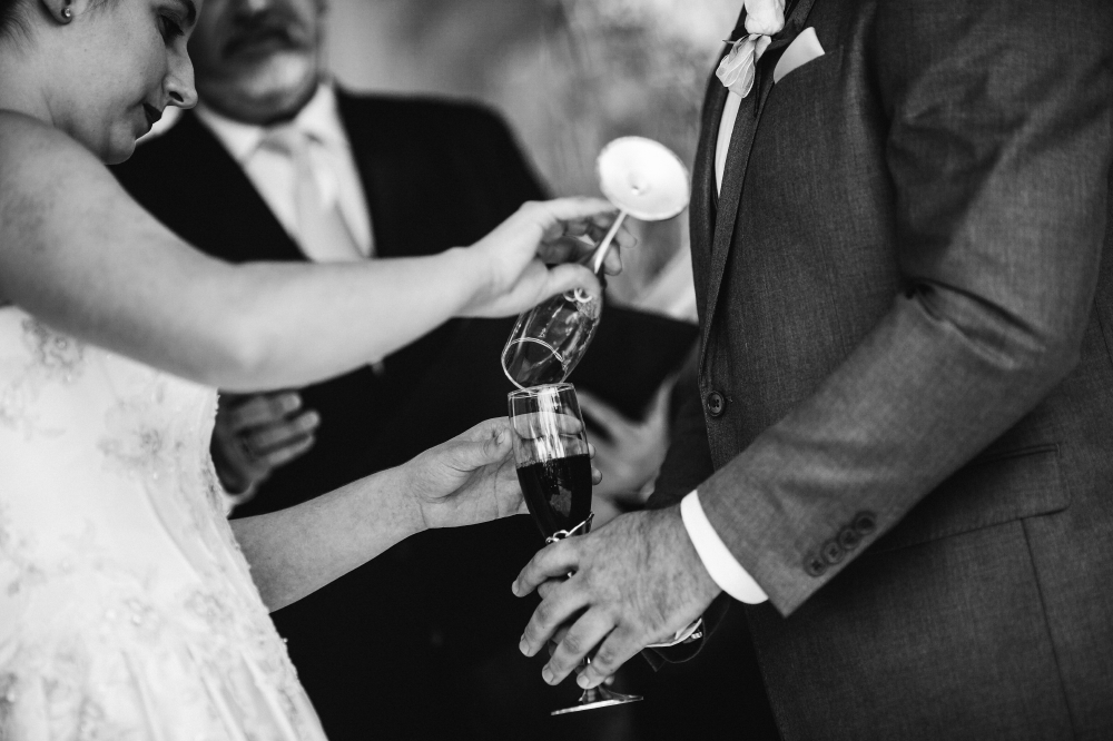 san diego wedding   photographer   woman pouring contents of her wine glass into groom's wine   glass