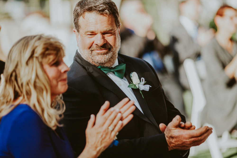 san diego wedding   photographer   man in black suit and dark teal bow tie looking to woman at   his side