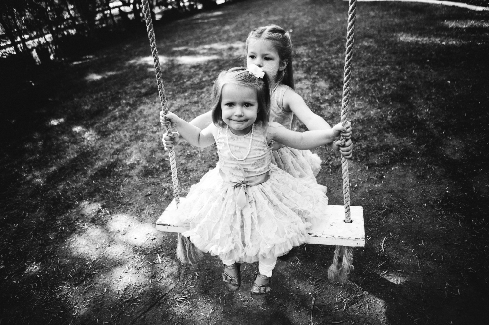 san diego wedding   photographer   monotone shot of children playing in swing