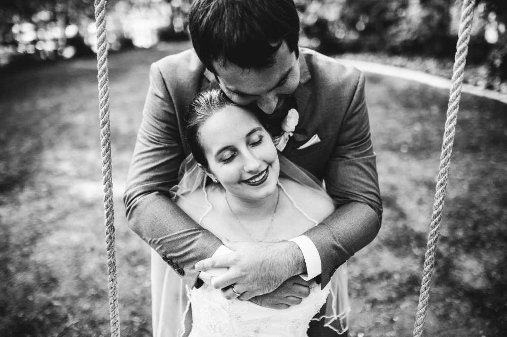 san diego wedding   photographer   monotone shot of bride on swing being hugged by groom from   behind