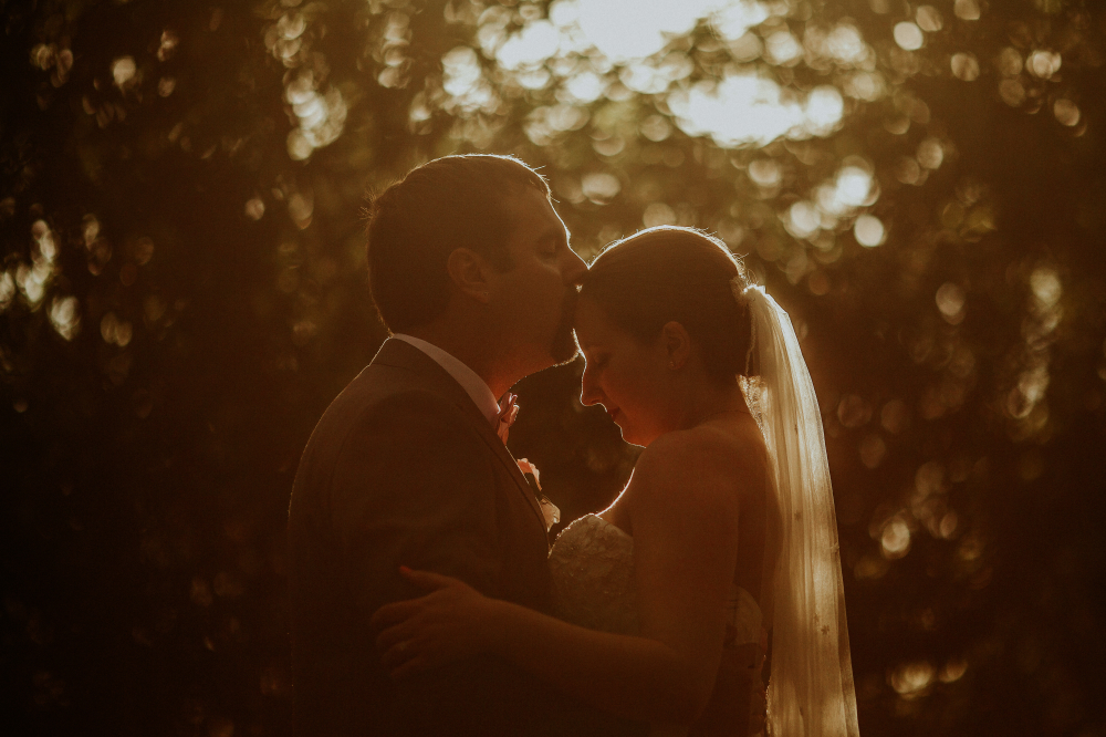 san diego wedding   photographer | groom about to kiss bride's forehead with sunset behind them