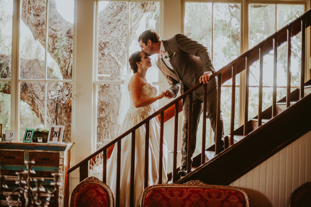 san diego wedding   photographer   groom kissing bride's forehead from above on stairs