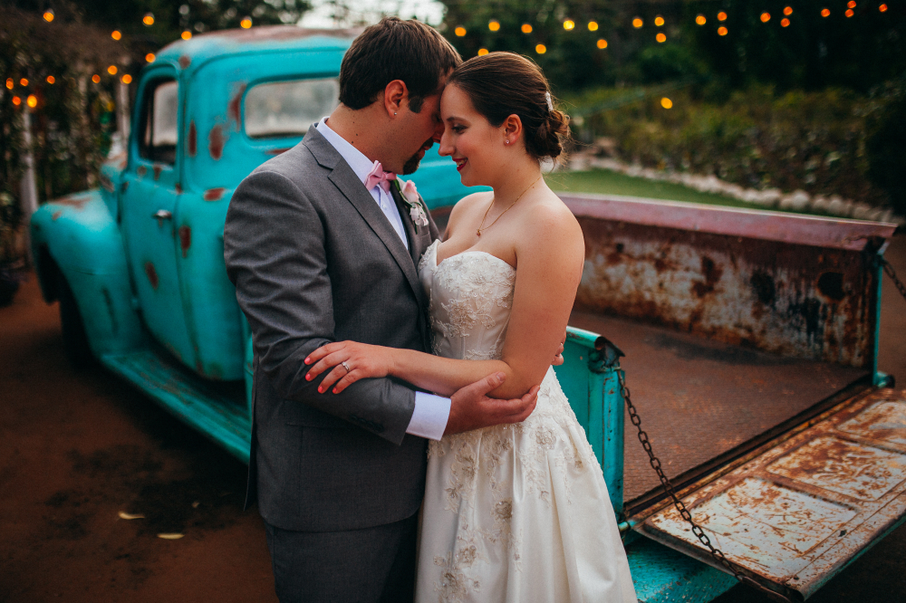 san diego wedding   photographer   bride and groom holding each other behind light blue pick up   truck