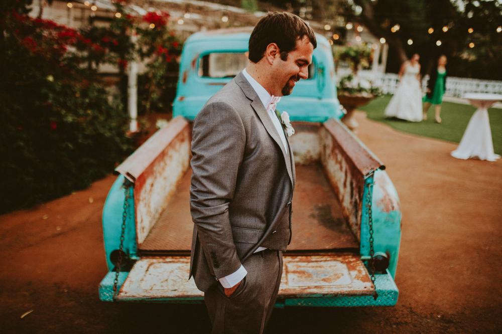 san diego wedding   photographer   man standing smiling behind light blue pickup truck