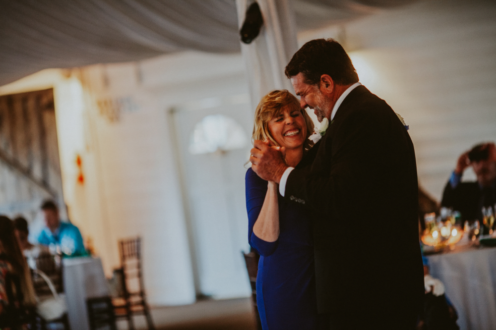 san diego wedding   photographer   woman in deep blue dress dancing with man in suit   laughing