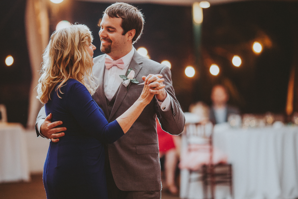 san diego wedding   photographer   groom dancing with middle aged woman in deep blue dress