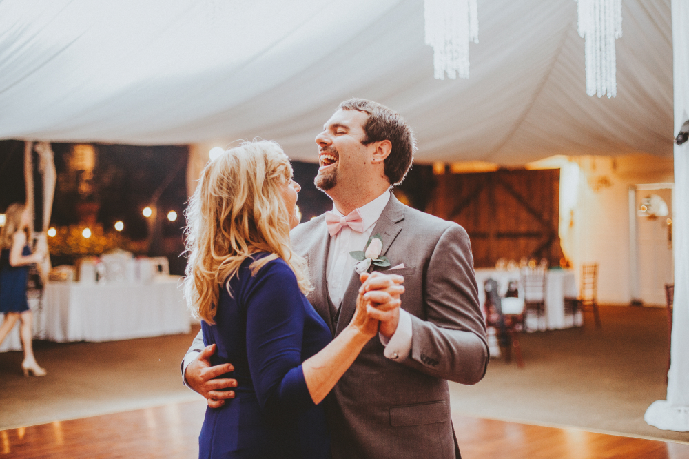 san diego wedding   photographer   groom dancing with middle aged woman in deep blue dress   laughing