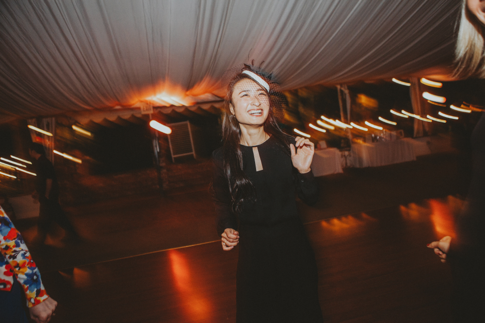 san diego wedding   photographer   woman in black dress laughing in middle of dance floor
