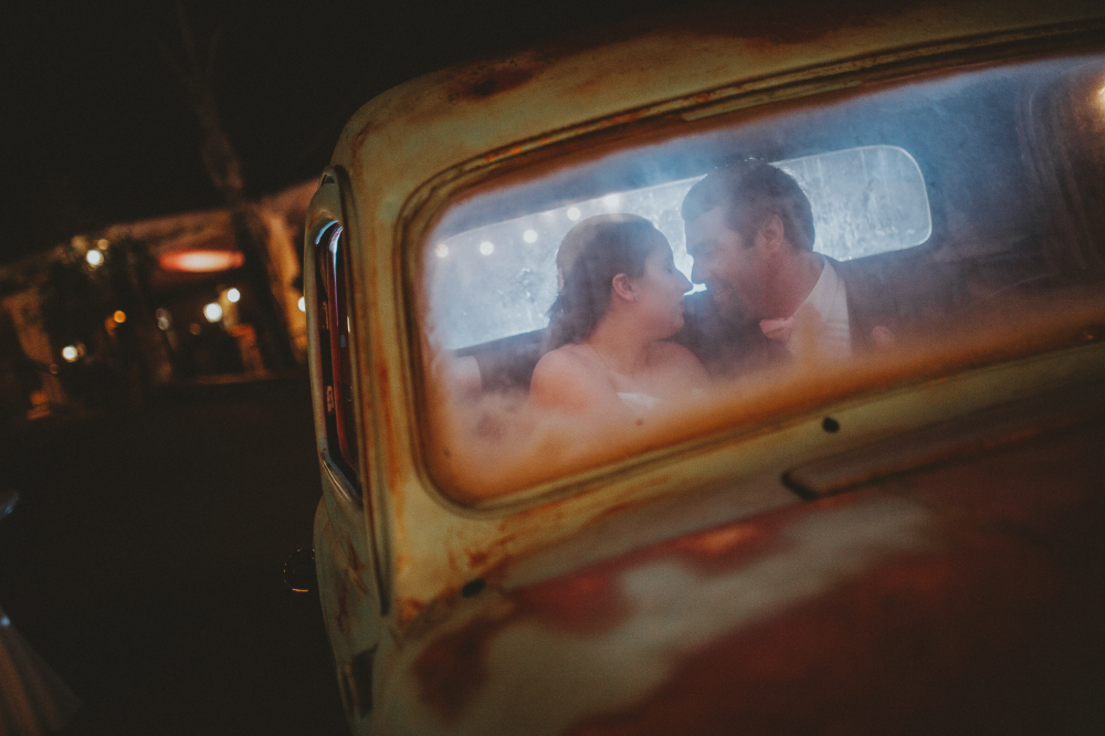 san diego wedding   photographer   bride and groom about to kiss each other seen through dirty   windshield