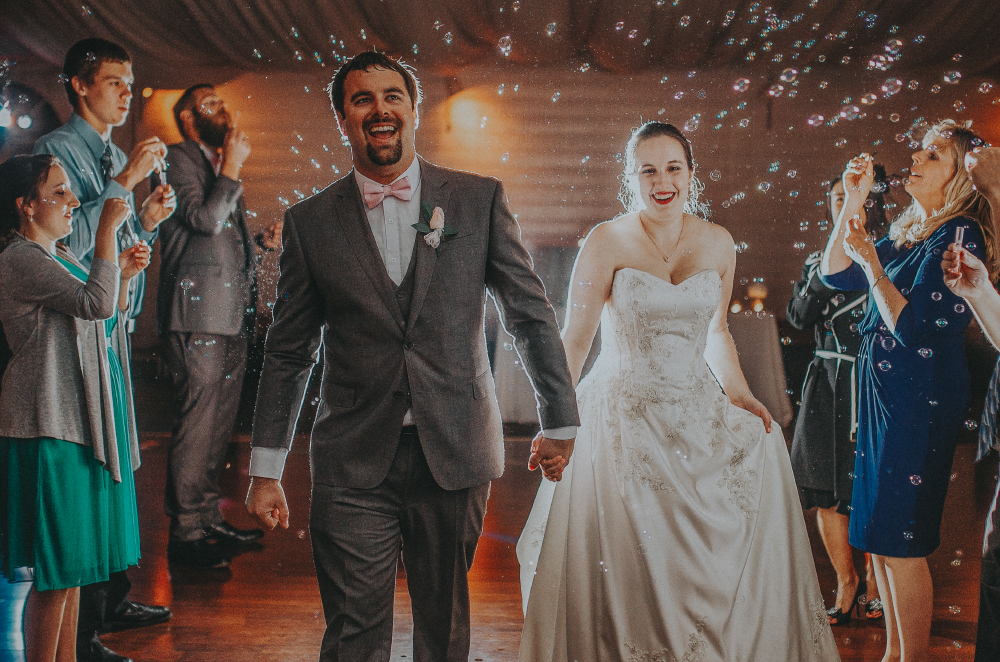 san diego wedding   photographer   newly wed couple with light behind them walking surrounded by   bubbles