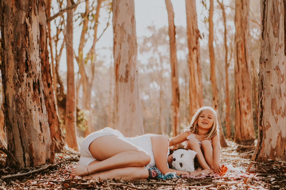 san diego wedding   photographer   child sitting down with woman in mask laying beside her