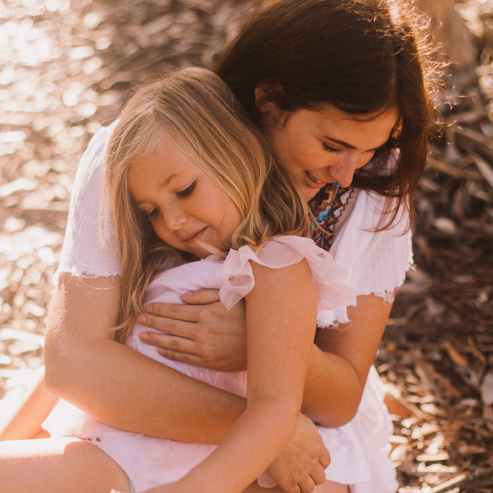 san diego wedding   photographer   child being hugged by woman in white from behind