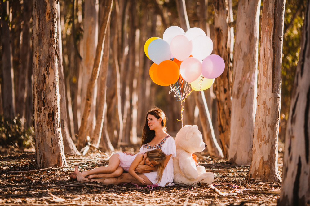 san diego wedding   photographer   child sleeping on mother's lap with white stuffed bear behind   them