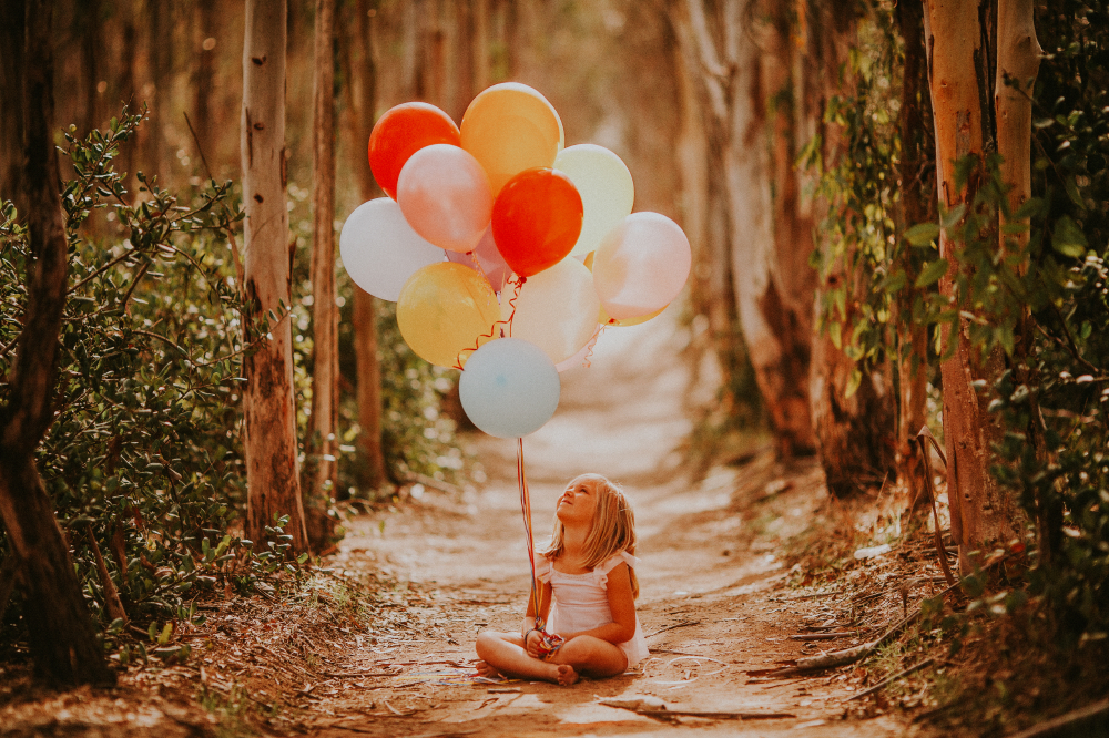 san diego wedding   photographer   child sitting in the middle of pathway looking up to colorful   balloons