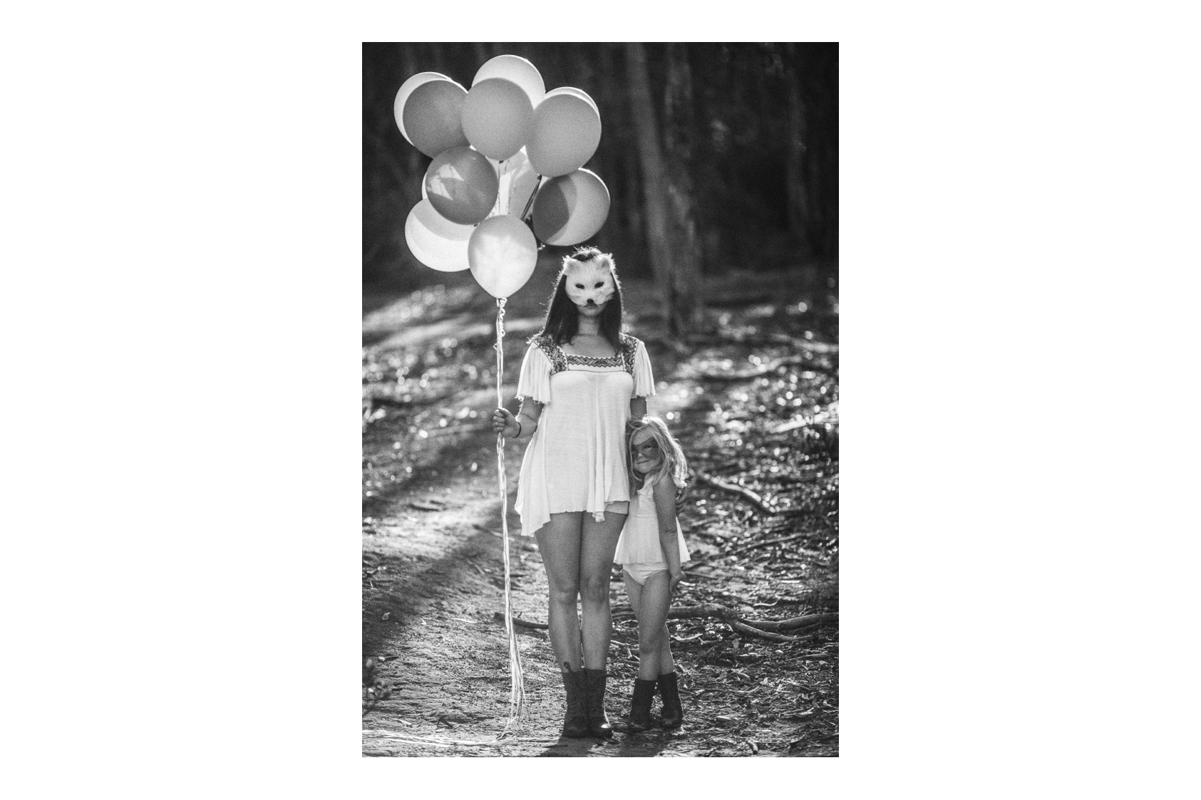 san diego wedding   photographer   monotone shot of child and woman in masks with balloons