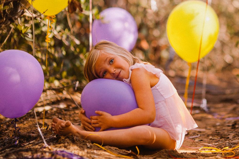 san diego wedding   photographer   child hugging purple balloon