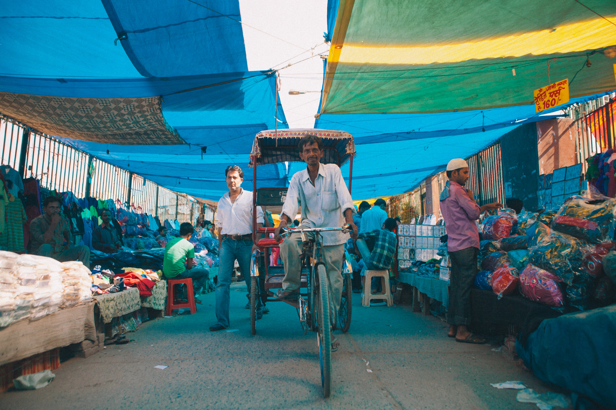 san diego wedding   photographer | man riding rickshaw under street covered in blue tarp