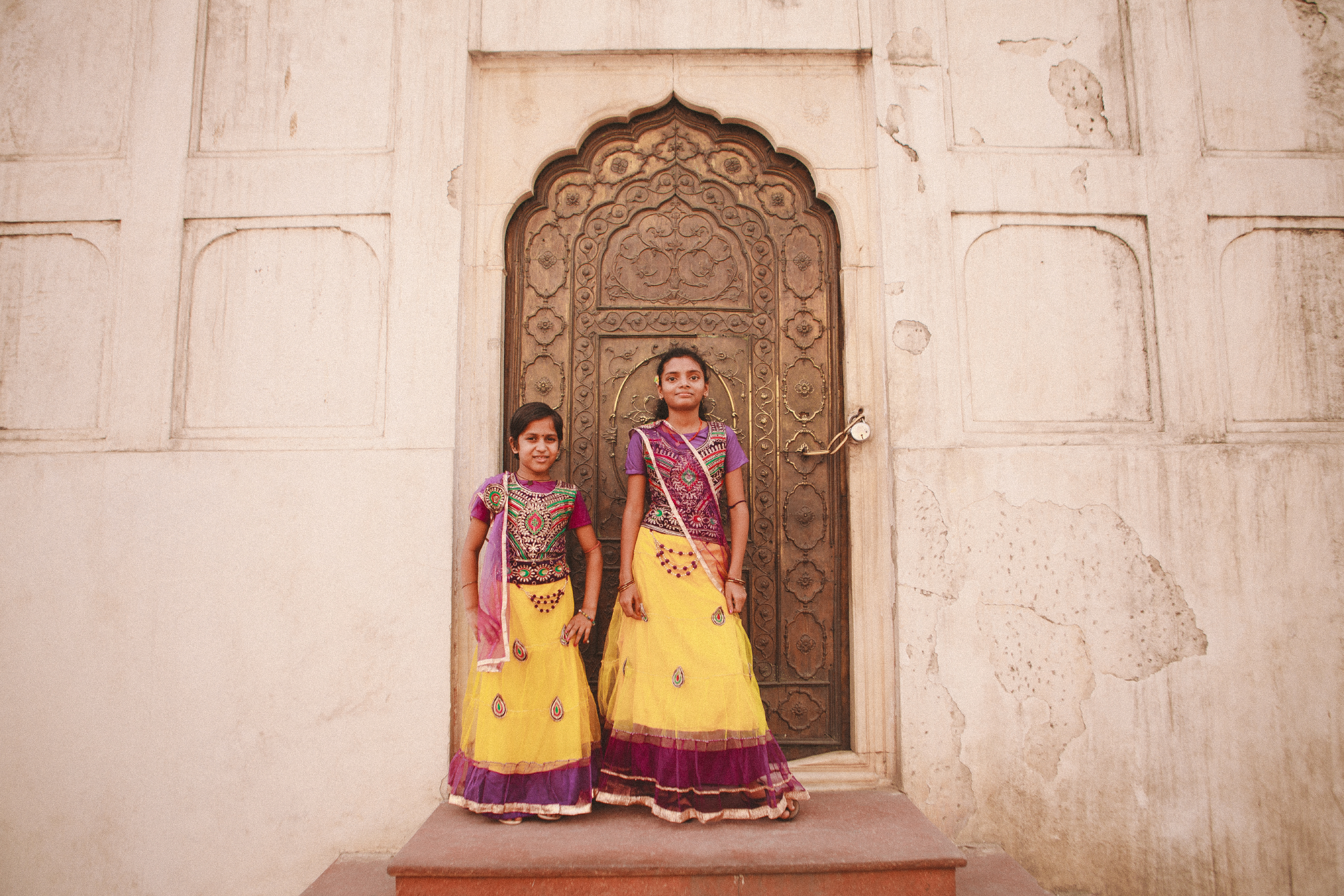 san diego wedding   photographer | indian girls wearing traditional outfit standing in front of   door