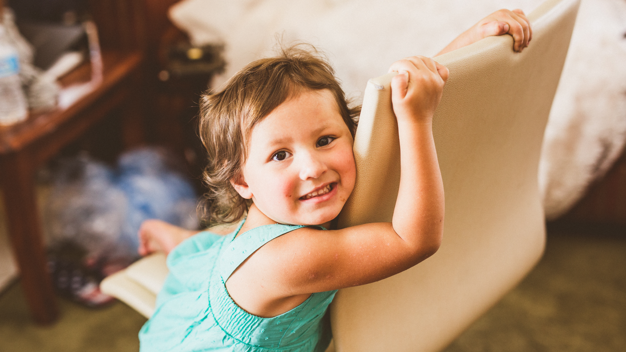 san diego wedding   photographer   child in pastel dress leaning against chair