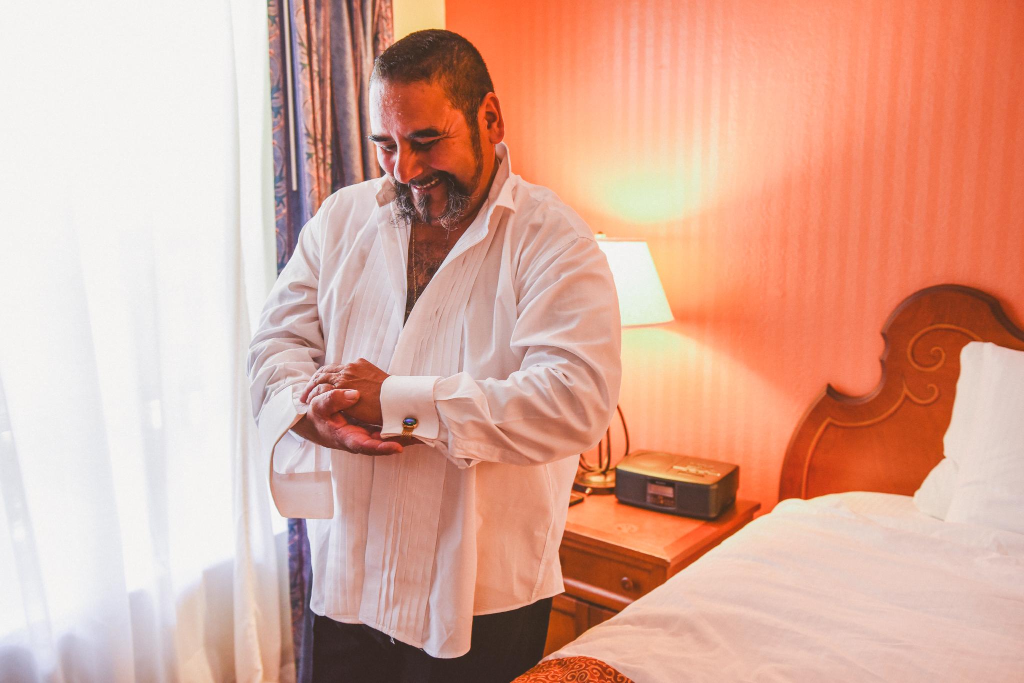 san diego wedding   photographer   man putting on white button down shirt smiling looking down