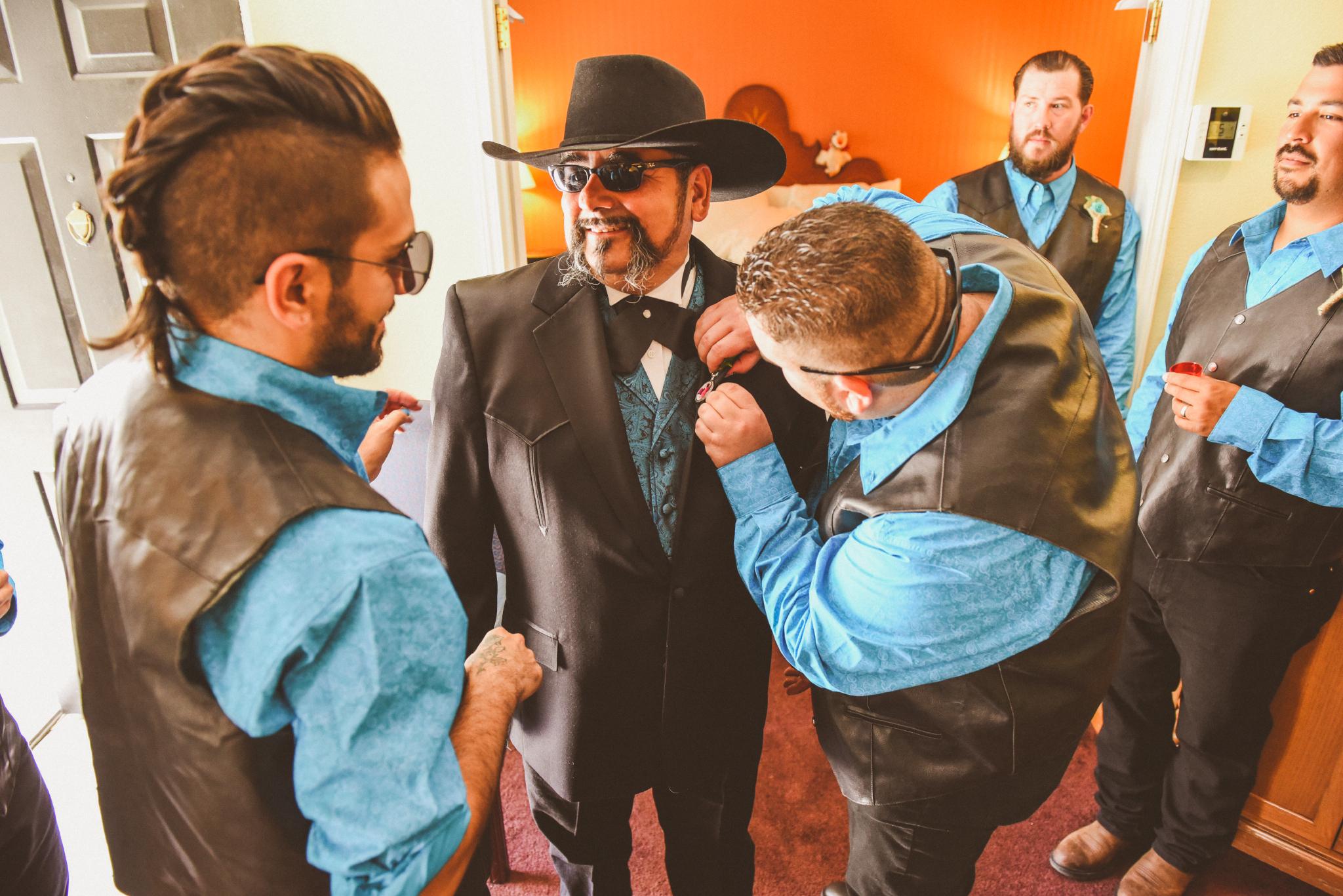 san diego wedding   photographer   men in turquoise helping man in cowboy hat dress