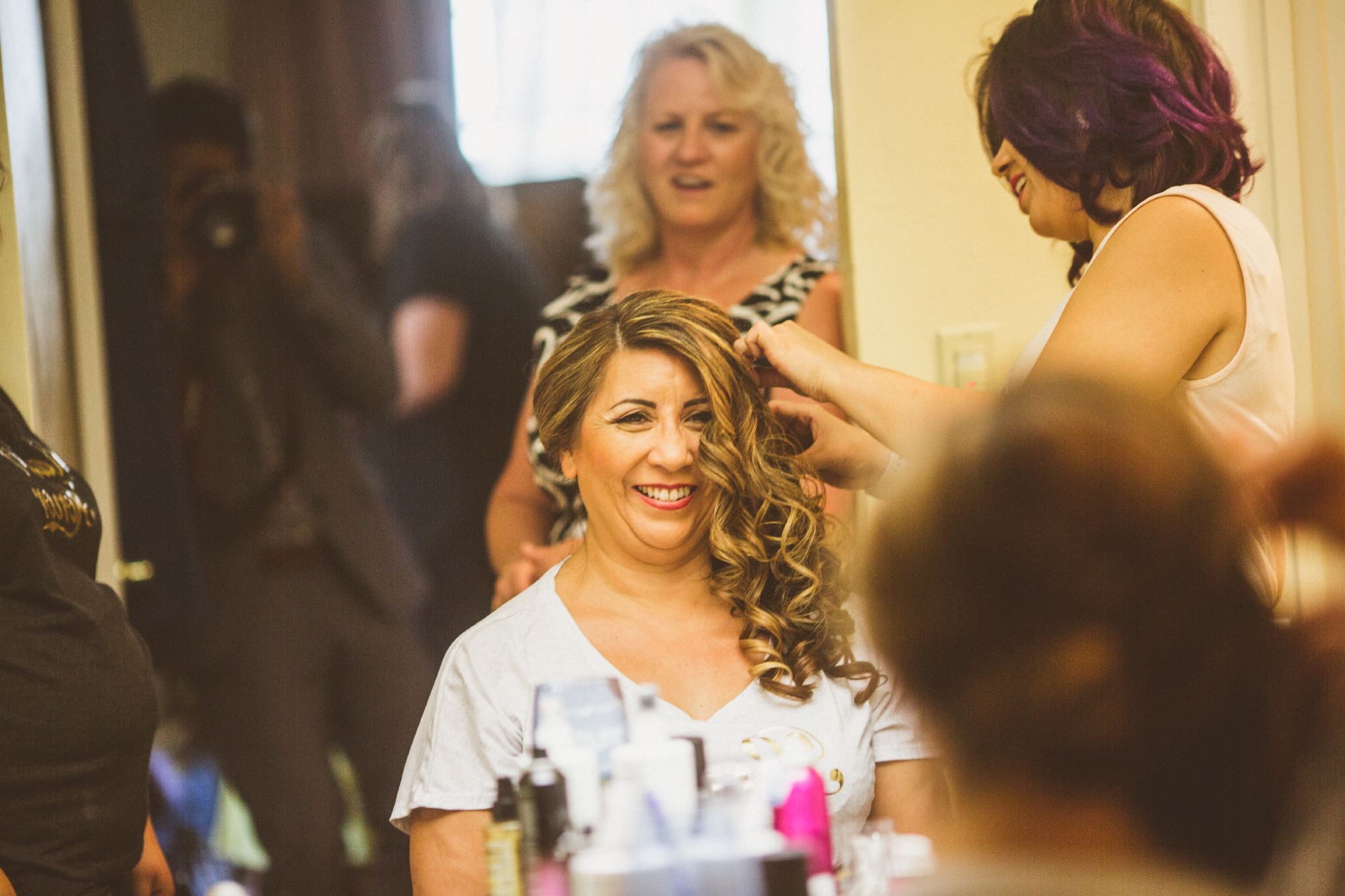san diego wedding   photographer   woman in white looking into mirror getting her hair fixed