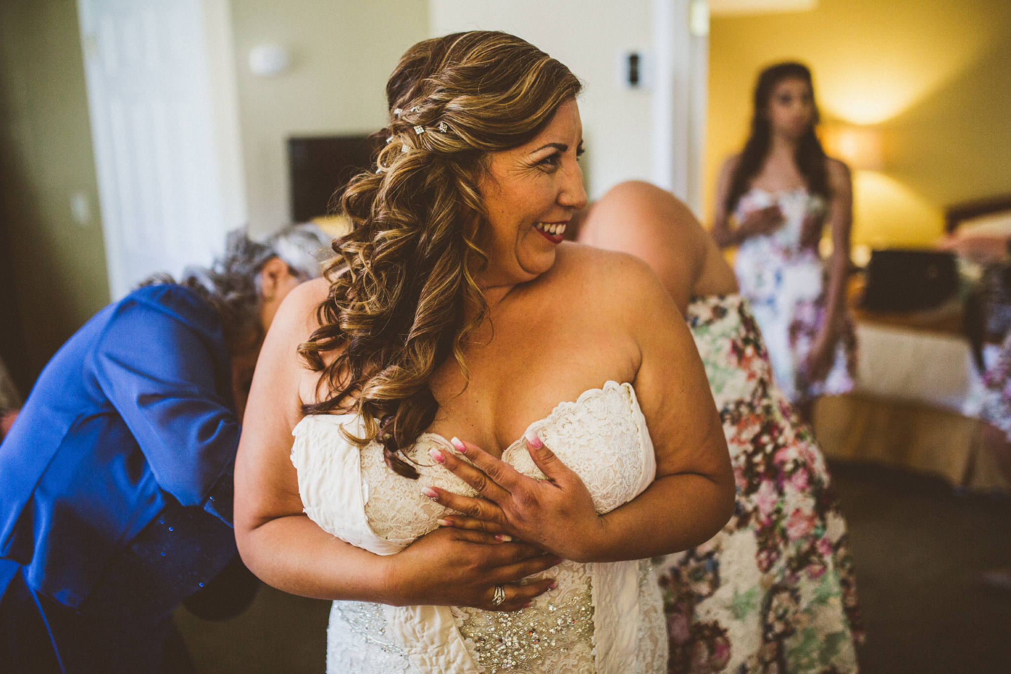 san diego wedding   photographer   women in blue and floral dress helping bride get dressed