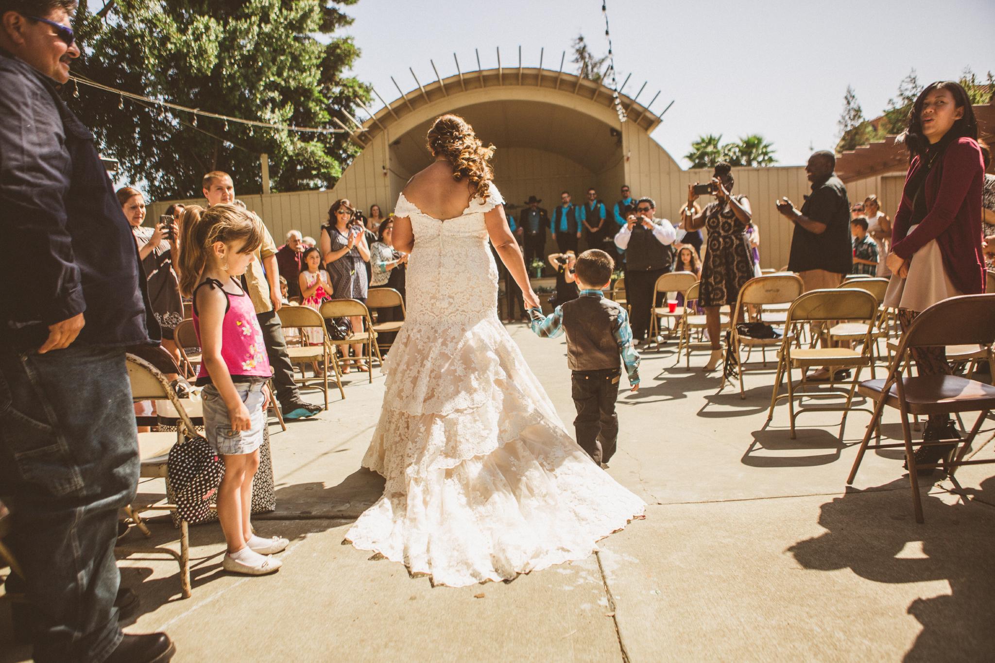 san diego wedding   photographer   bride holding child's hand walking down aisle