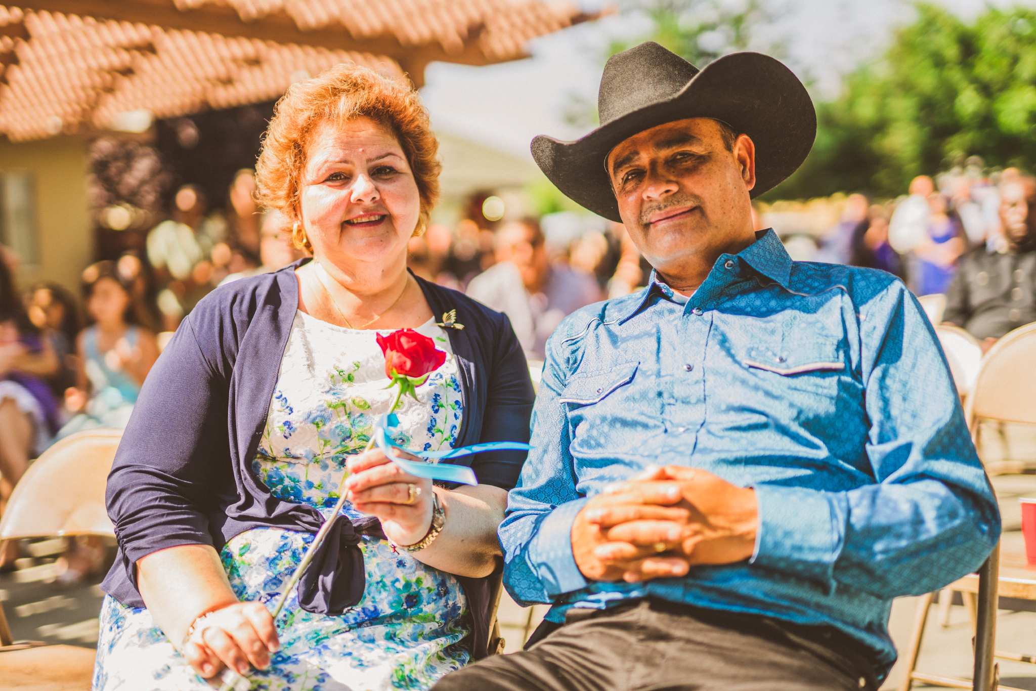 san diego wedding   photographer   man and woman in crowd sitting looking at camera
