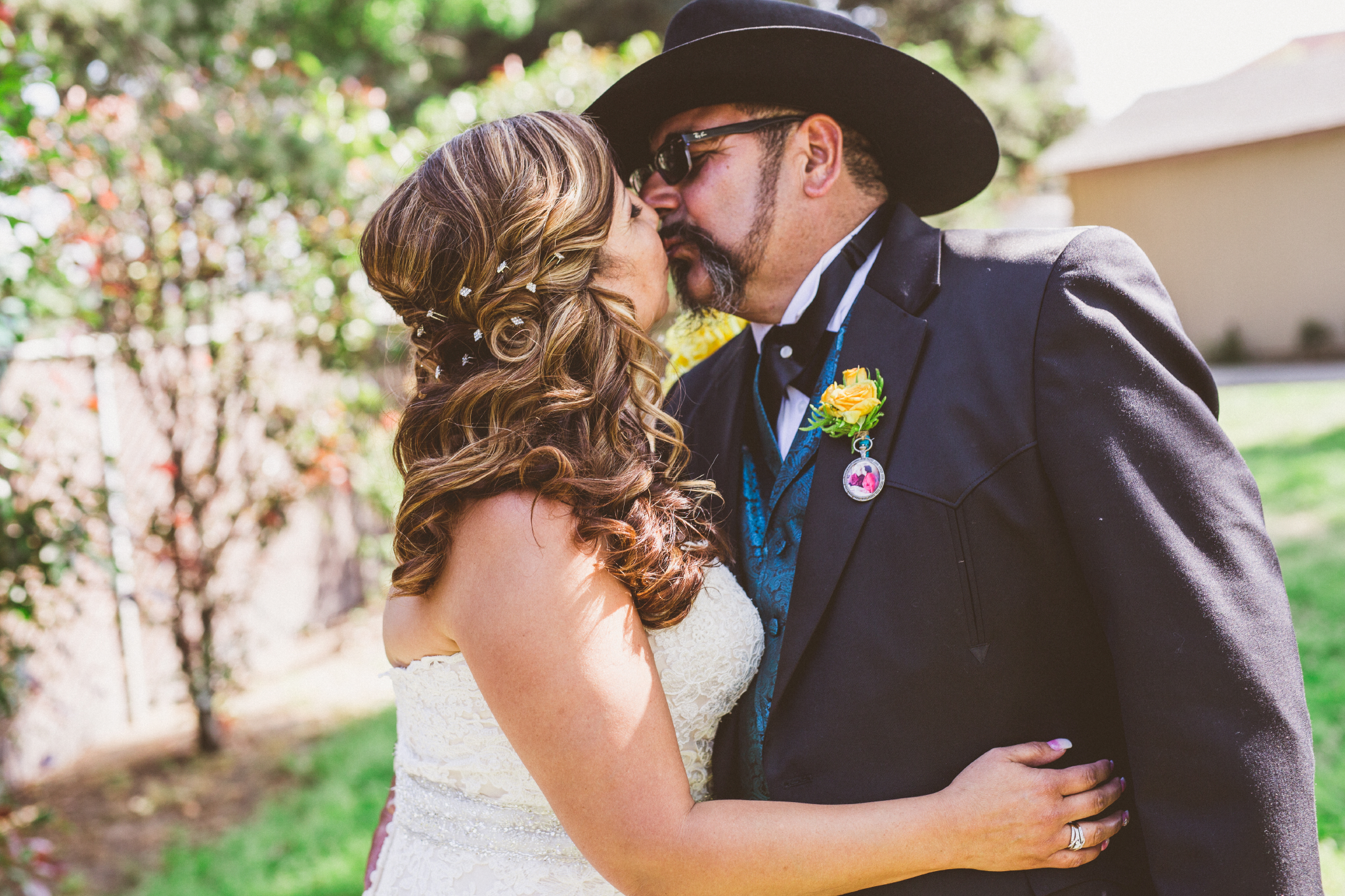 san diego wedding   photographer   bride and groom in cowboy hat about to kiss on yard