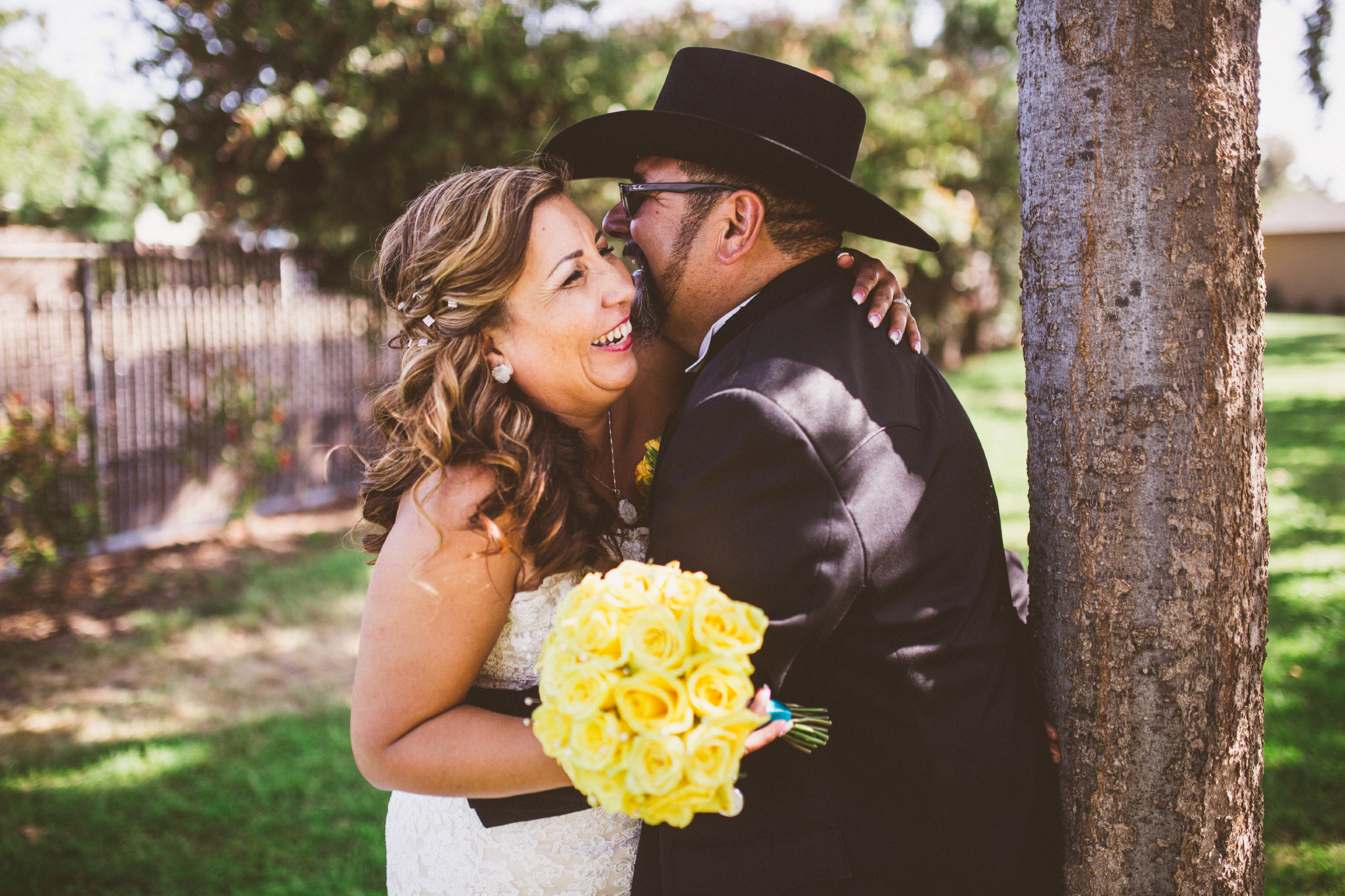 san diego wedding   photographer   groom with cowboy hat and bride leaning close to each other   and leaning against tree