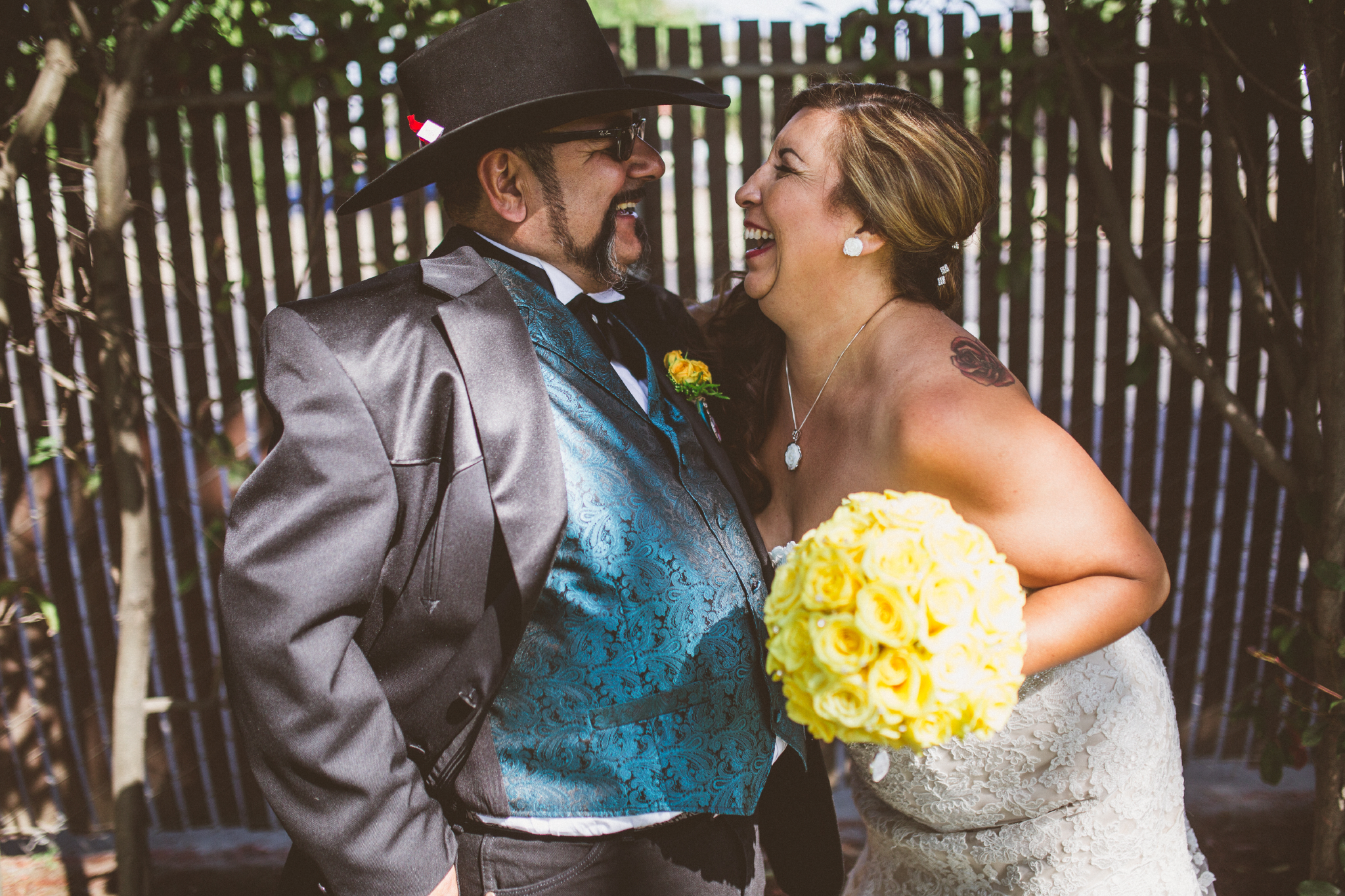 san diego wedding   photographer   bride and groom laughing with wooden fence behind them